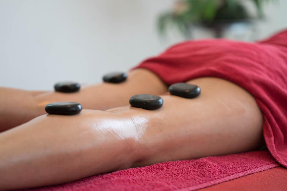 Hot-Stone Massagesteine auf den Beinen einer Patientin